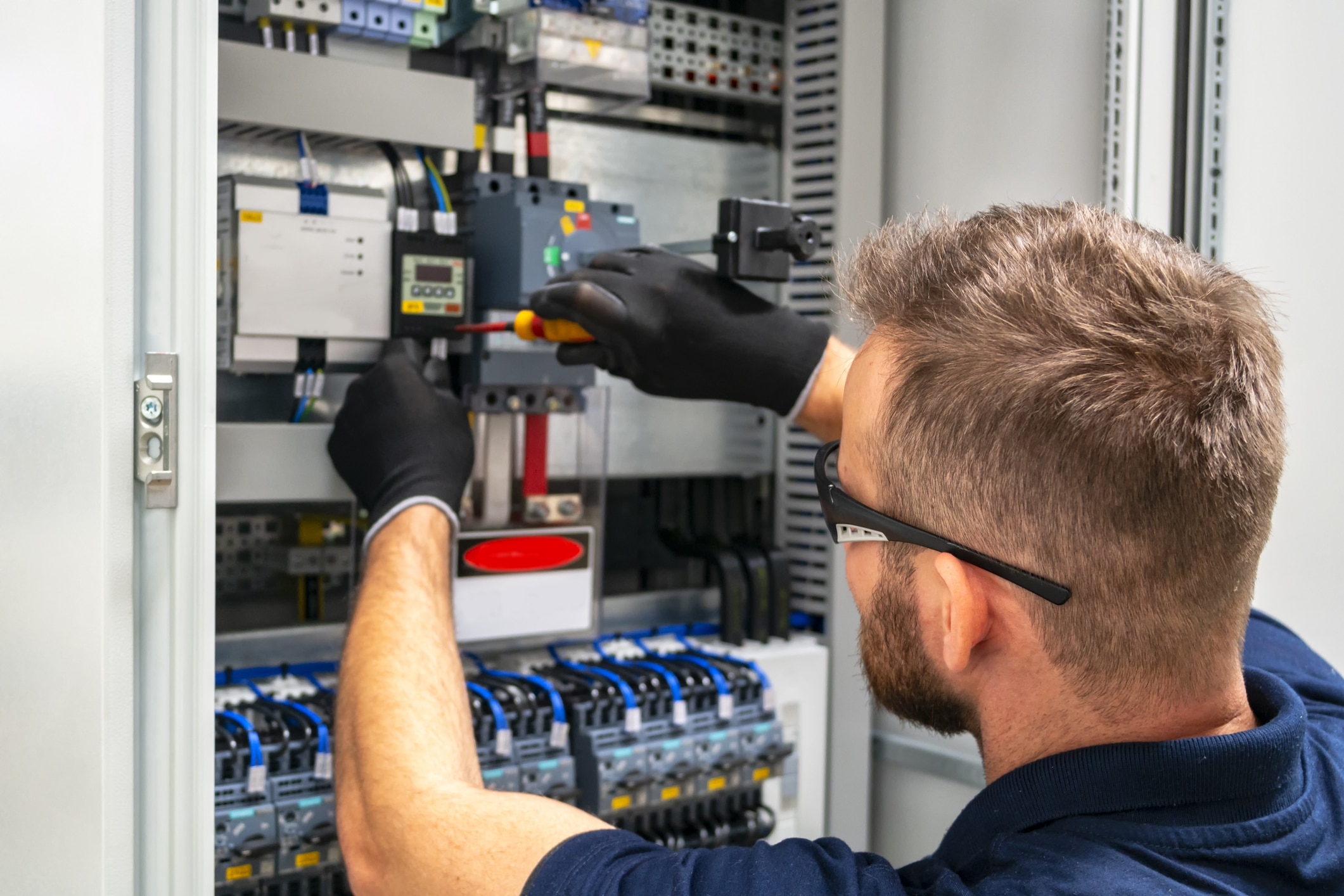 Photo of an electrician working at distribuition board.
